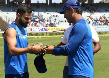 MS Dhoni hands over the camouflage military cap to Virat Kohli prior to the start of the third ODI against Australia at Ranchi, Friday