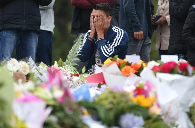 People pay their respects in front of floral tributes for victims of the March 15 mosque attacks, in Christchurch (AFP)
