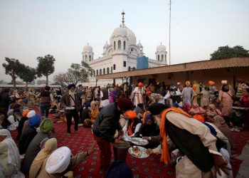 A man serves food to Sikhs from India outside the shrine of Guru Nanak Dev Ji, founder of Sikhism, during the groundbreaking ceremony of the Kartarpur border corridor, which will officially open next year, in Kartarpur, Pakistan November 28, 2018. REUTERS/Mohsin Raza/Files