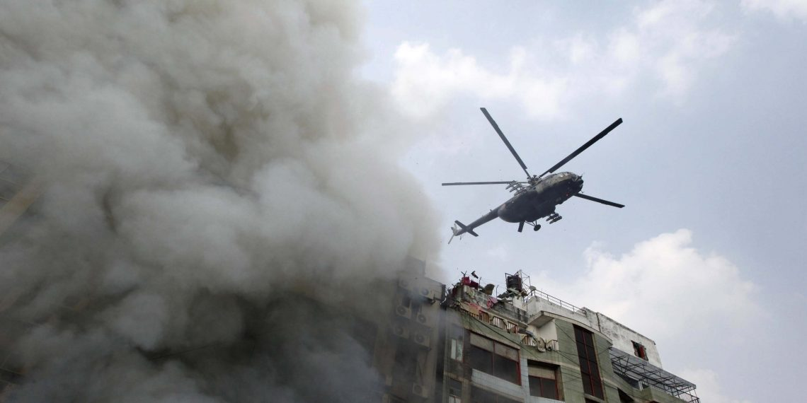 As smoke comes out of the building in Dhaka a helicopter hovers over it to find out trapped people