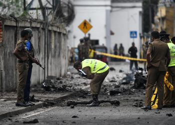 Sri Lankan security personnel inspect the debris of a van after it explodes on Monday near St. Anthony's Shrine in Colombo. Nearly 300 people died and more than 500 others were wounded after Sunday's attacks on churches and hotels.
