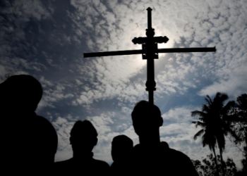 A man holds a cross during a mass burial of victims of the Easter Sunday bombings, at a cemetery in Sri Lanka, April 23