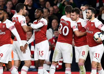 Arsenal players congratulate Aaron Ramsey (8) after he scored the first goal for his team, Monday