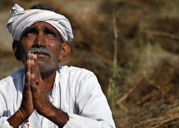 An Indian farmer looks skyward as he sits in his field with wheat crop that was damaged in unseasonal rains and hailstorm at Darbeeji village, in the western Indian state of Rajasthan, Friday, March 20, 2015. Recent rainfall over large parts of northwest and central India has caused widespread damage to standing crops. (AP Photo/Deepak Sharma)