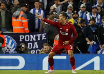 Roberto Firmino points to the fans in celebration after scoring the second goal for Liverpool against Porto, Tuesday