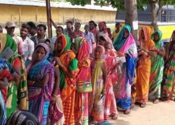 Women voters await their turn under sun at a booth in Purushottampur in Ganjam district, Thursday 	op photo