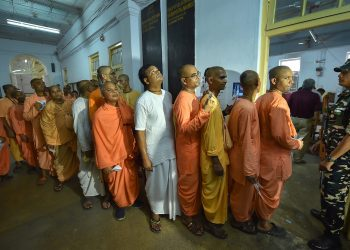 Members of ISKCON wait to cast their votes for the seventh and last phase of Lok Sabha elections, at a polling booth in Kolkata, Sunday