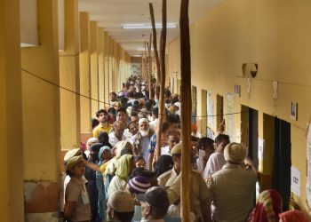 Voters queue up to cast their votes at a polling booth in New Delhi, Sunday