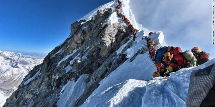 """TOPSHOT - This handout photo taken on May 22, 2019 and released by climber Nirmal Purja's Project Possible expedition shows heavy traffic of mountain climbers lining up to stand at the summit of Mount Everest. - Many teams had to line up for hours on May 22 to reach the summit, risking frostbites and altitude sickness, as a rush of climbers marked one of the busiest days on the world's highest mountain. (Photo by Handout / Project Possible / AFP) / RESTRICTED TO EDITORIAL USE - MANDATORY CREDIT """"AFP PHOTO / PROJECT POSSIBLE"""" - NO MARKETING NO ADVERTISING CAMPAIGNS - DISTRIBUTED AS A SERVICE TO CLIENTS ---HANDOUT/AFP/Getty Images"""