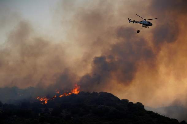 A helicopter flies over a wildfire near the city of Toledo, Spain June 28
