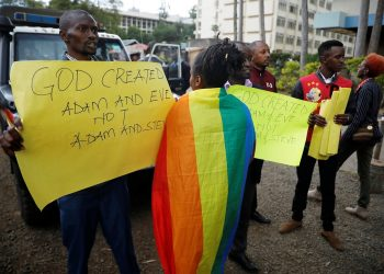 An LGBT activist walks past anti-gay rights protesters holding placards, after a ruling by Kenya's high court to upheld a law banning gay sex, outside the Milimani high Court in Nairobi