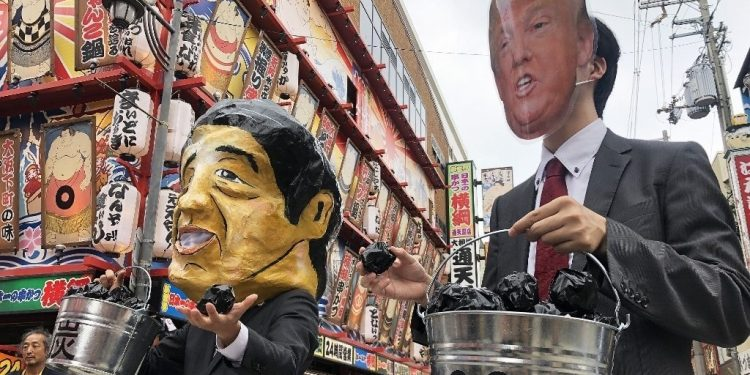 Protesters wearing masks of world leaders including a giant paper mache Japanese Prime Minister Shinzo Abe (L) and US President Donald Trump demonstrate against climate change and coal use, at Osaka in Japan