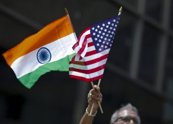 A man holds the flags of India and the U.S. while people take part in the 35th India Day Parade in New York August 16, 2015. REUTERS/Eduardo Munoz - GF20000022053
