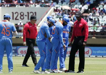 Indian players and umpires inspect the pitch after a rain break during their first ODI match against The West Indies, Thursday in Providence