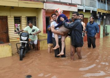 An elderly woman being carried to safety in Kerala's Wayanad district
