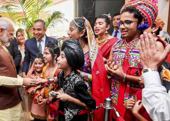 Prime Minister Narendra Modi reacts with Indian people in Manama