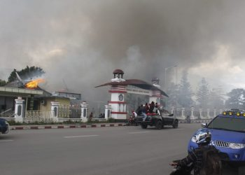 People drive past a blazing government building in Wamena, Monday