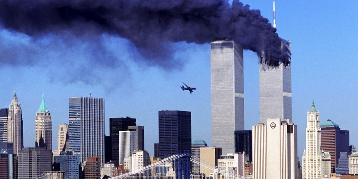 One of the twin towers in New York burning with the second one about to get hit