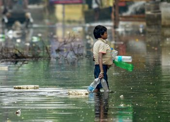 As flood waters recede in Patna a ragpicker collects debris
