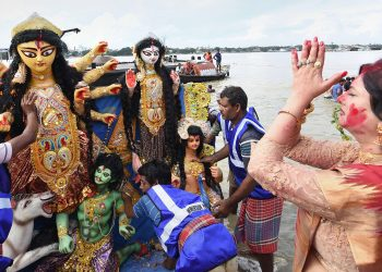 A devotee prays as an idol of Maa Durga is about to be immersed in the Ganges at Kolkata