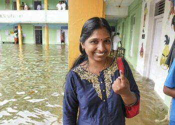 A woman shows her finger marked with indelible ink after casting her vote at a polling station inundated in rain water in Ernakulam