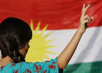A protester in front of a Kurdish flag.