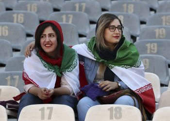Iranian women wear their country's flag on their shoulders at the Azadi Stadium for the 2022 World Cup Qualifier soccer match between Iran and Cambodia