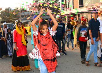 A girl swirling a decorative wheel during a procession for celebration of Guru Nanak Dev's 550th birth anniversary in Sambalpur