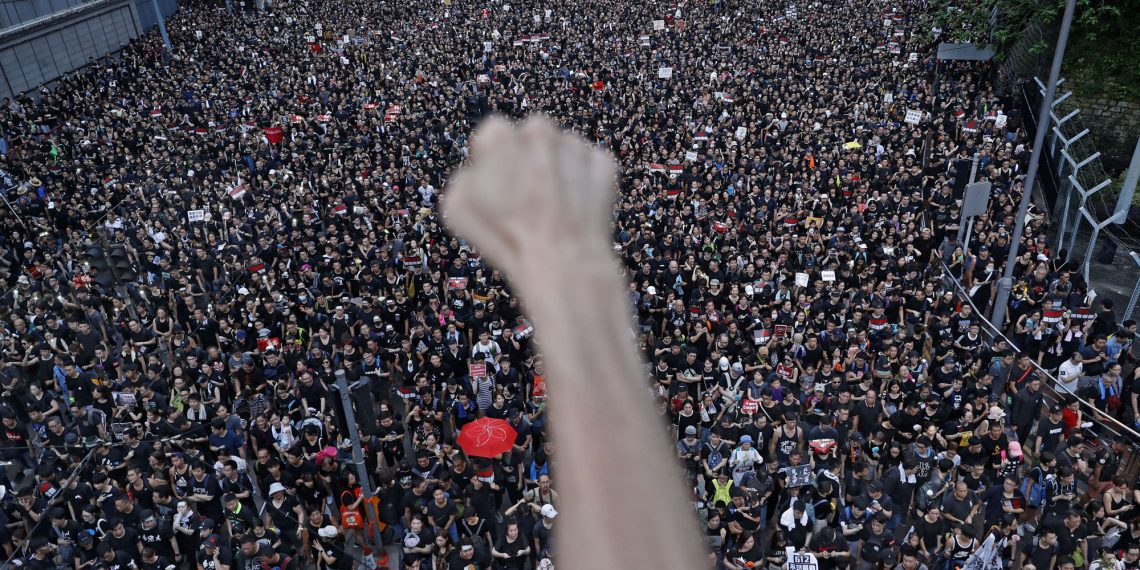 FILE - In this Sunday, June 16, 2019, file photo, a protester clenches his fist as tens of thousands of protesters march on the streets to stage a protest against the unpopular extradition bill in Hong Kong. (AP Photo/Vincent Yu, File)