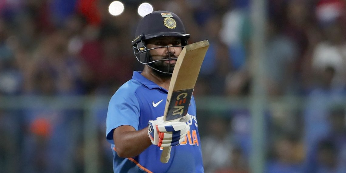Rohit Sharma raises his bat after reaching his century at Bangalore against Australia