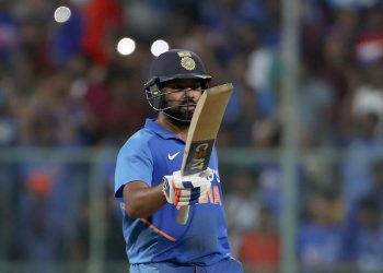 Rohit Sharma raises his bat after reaching his century at Bangalore against Australia