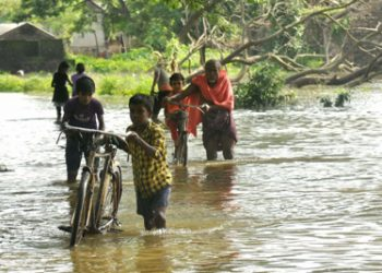 File photo of villagers wading through a flooded street at Banki in Cuttack
