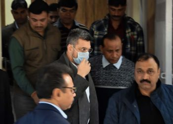 Bookie Sanjeev Chawla (face covered) being escorted out of the Delhi Airport by Crime Branch officers