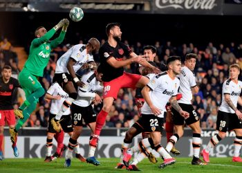 Valencia's Spanish goalkeeper Jaume Domenech (L) jumps for the ball during the Spanish league football match between Valencia CF and Club Atletico de Madrid at the Mestalla stadium in Valencia on February 14, 2020. (Photo by JOSE JORDAN / AFP)