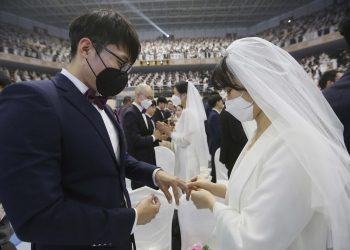 A couple wearing face masks exchanges their rings in a mass wedding ceremony at the Gapyeong in South Korea