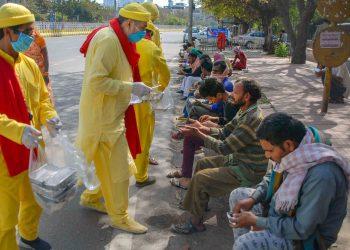Volunteers distribute food to migrant workers in Noida Tuesday