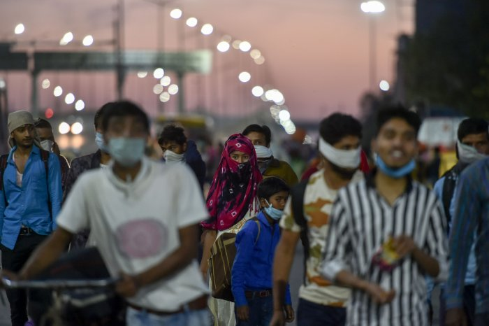 Migrants, along with their family members, walk to their villages amid the nationwide lockdown, in the wake of coronavirus pandemic, at Delhi-Uttar Pradesh border. (PTI Photo)