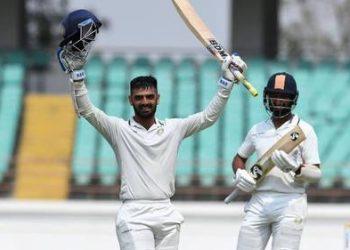 Arpit Vasavada raises his bat after century as Cheteshwar Pujara appreciates in Rajkot, Tuesday