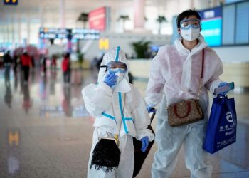 A lady and her son at the Wuhan Airport, Wednesday