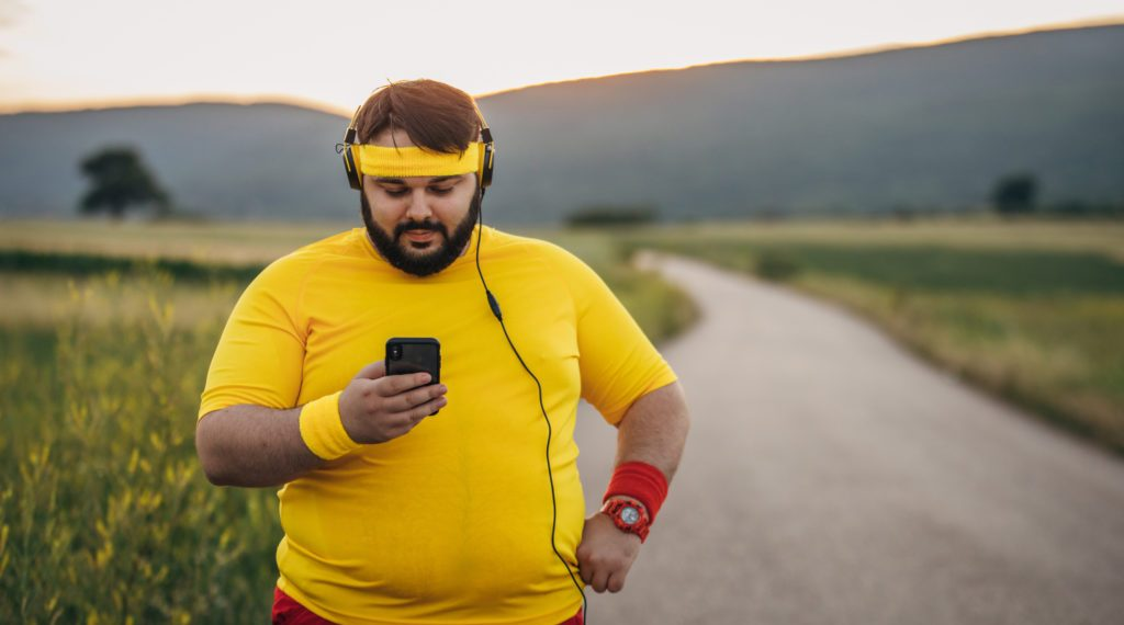 One man, young overweight man break after jogging, listening music on headphones, using smart phone.