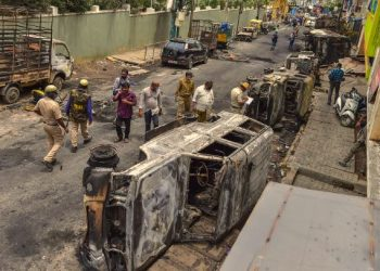 Bengaluru: Police and residents walk past charred remains of vehicles vandalised by a mob over a social media post, allegedly by a relative of a Congress MLA, in Bengaluru, Wednesday, Aug. 12, 2020. (PTI)