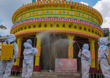 Members of committee Durga Puja wearing PPE kit sanitise a puja pandal in the wake of coronavirus pandemic. (Photo: PTI)