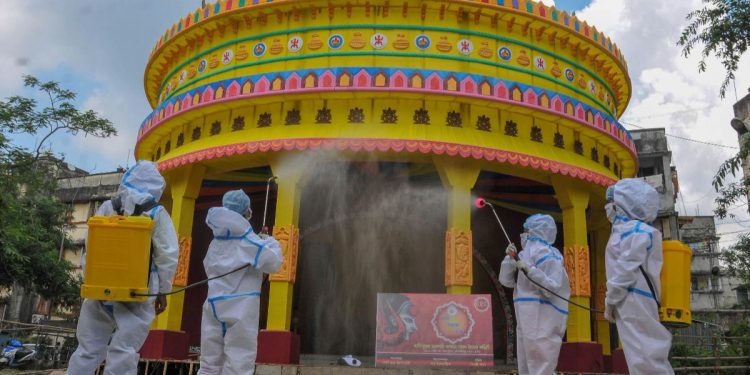 Members of committee Durga Puja wearing PPE kit sanitise a puja pandal in the wake of coronavirus pandemic. (Photo: PTI)
