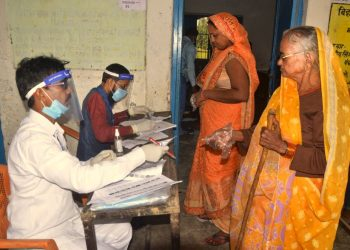 Rohtas: Polling officials check the names of voters at a polling booth as they arrive to cast their votes for the first phase of Bihar Assembly Election, amid the coronavirus pandemic, at Chenari police station in Rohtas district, Wednesday, Oct. 28, 2020. (PTI Photo)