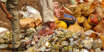 A Malgodown police official disposing of a huge amount of adulterated spice packets near Sikharpur area in Cuttack, Monday