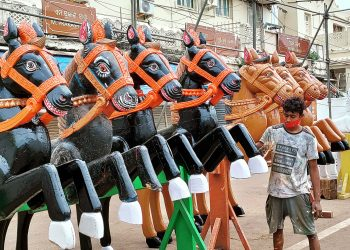 A servitor paints wooden horses ahead of the Rath Yatra in Puri, Sunday
