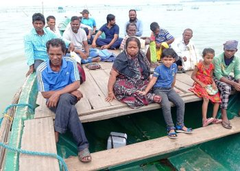 Health workers carry Covid-19 swab samples on passenger boats